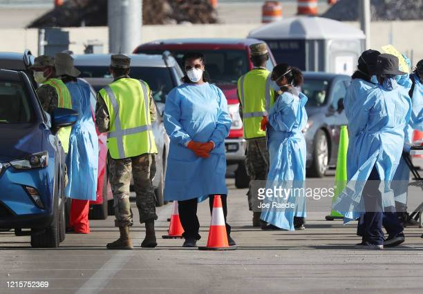 Health care workers check in people at a testing site setup by the the Florida National Guard in the parking lot of the Hard Rock stadium on March 30...