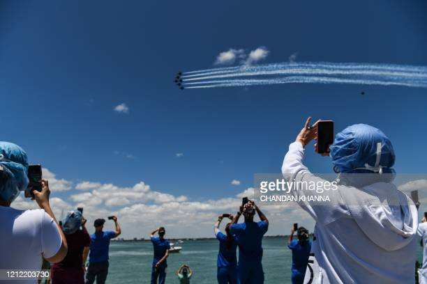 Health care workers gather by the bay to watch the US Navy Blue Angels and US Air Force Thunderbirds fly over the Mount Sinai Medical Center in Miami...