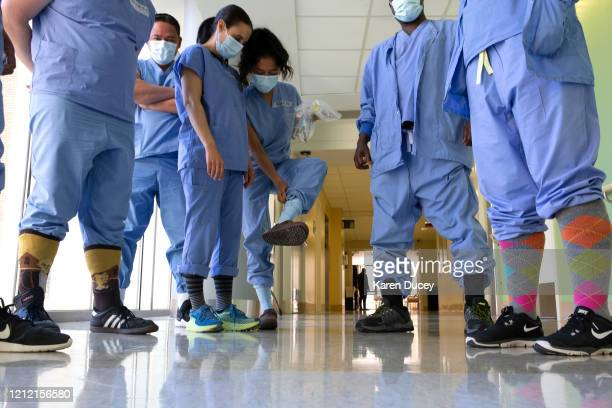 Health care workers in the acute care COVID unit at Harborview Medical Center show off their covid socks on May 7 2020 in Seattle Washington Medical...