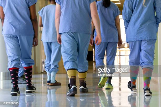 Health care workers in the acute care COVID unit at Harborview Medical Center walk down a hallway in their covid socks on May 7 2020 in Seattle...