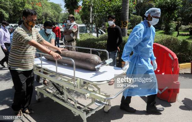 Health care workers rushing with an oxygen cylinder on a stretcher at Jaipur Golden hospital where at least 25 Covid-19 patient passed away while in...