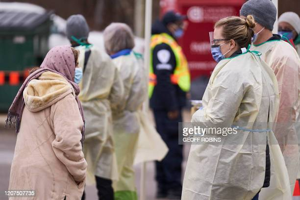 Health care workers speak with an elderly woman at a Covid19 assessment center in London Ontario on March 17 2020 Canada is closing its borders to...