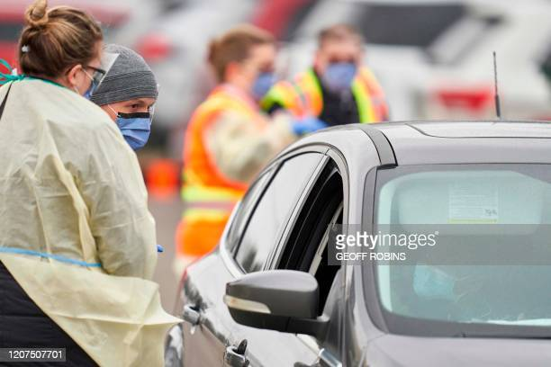 Health care workers speak with patients at a drivethru Covid19 assessment center in London Ontario on March 17 2020 Canada is closing its borders to...