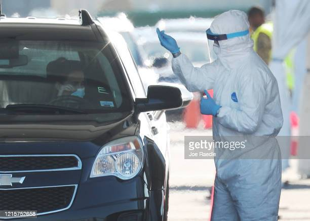 Health care workers test people at a coronavirus testing site setup by the the Florida National Guard in the parking lot of the Hard Rock stadium on...