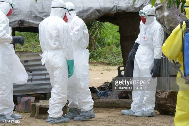 Health care workers wearing protective suits gather around a man infected with the Ebola virus lying unconscious in his house on September 4 2014 at...