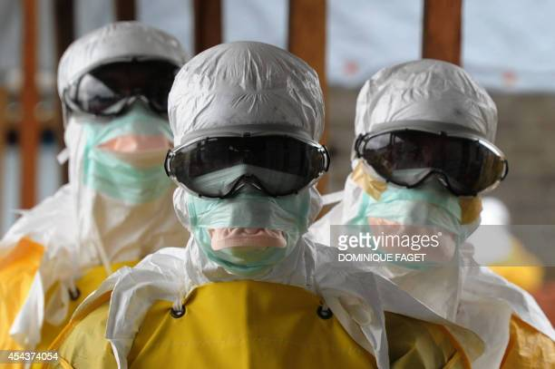 Health care workers wearing protective suits leave a highrisk area at the French NGO Medecins Sans Frontieres Elwa hospital on August 30 2014 in...