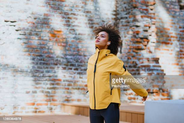 health conscious afro american sportswoman wearing a yellow track jacket stretching outdoors - coat stock pictures, royalty-free photos & images