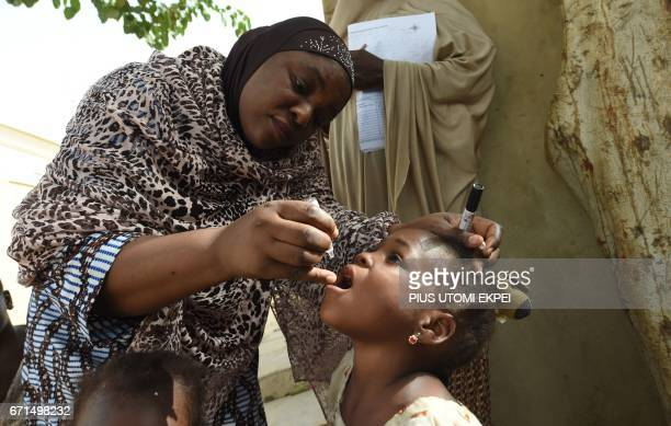 Health consultant Hadiza Waya tries to immunise a child during vaccination campaign against polio at Hotoro-Kudu, Nassarawa district of Kano in...