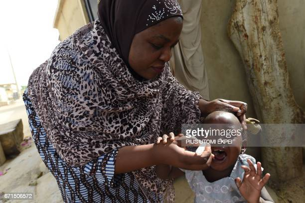 UNICEF health consultant Hadiza Waya tries to immunise a child during vaccination campaign against polio at HotoroKudu Nassarawa district of Kano in...