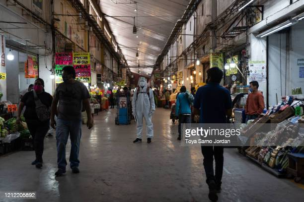 Health Department employee wearing safety equipment looks on at the Central de Abasto on May 8, 2020 in Mexico City, Mexico. The Central de Abasto is...