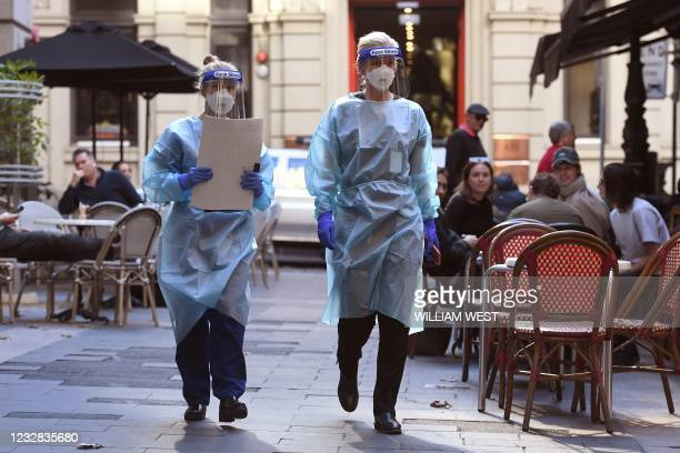 Health department officials arrive to inspect a restaurant and bar in Melbourne on May 12 after a man who had dined there later tested positive for...