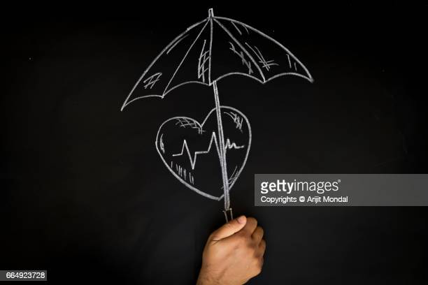 Health Insurance Concept Man Protecting Heart with Umbrella, Black Board Drawing