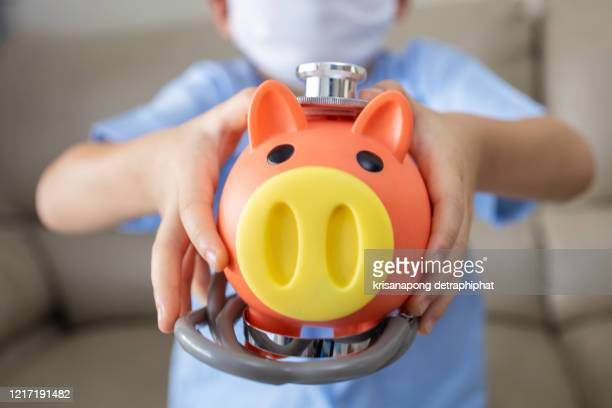health insurance concept,a child with a piggy bank - charity benefit stock pictures, royalty-free photos & images