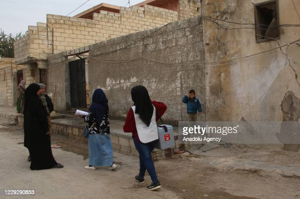 Health members of Sanliurfa Governorate's Syria Support and Coordination Center walk from door by door to find children to vaccinate during a polio...
