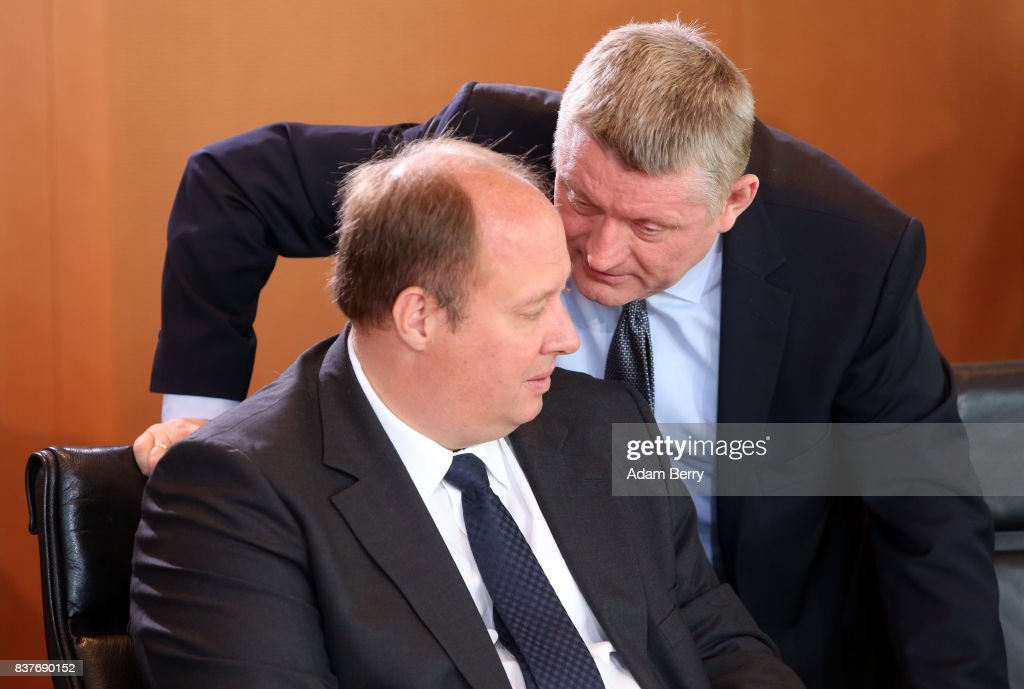 Health Minister Hermann Groehe (CDU, R) speaks to Minister of State Helge Braun (CDU) as they arrive for the weekly German federal Cabinet meeting on August 23, 2017 in Berlin, Germany. High on the meeting's agenda was discussion of government spending.