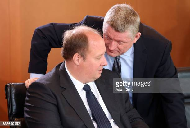 Health Minister Hermann Groehe speaks to Minister of State Helge Braun as they arrive for the weekly German federal Cabinet meeting on August 23 2017...