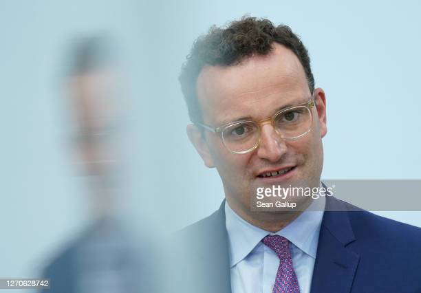 Health Minister Jens Spahn is reflected in glass as he speaks to the media following a virtual meeting with other EU health ministers and officials...