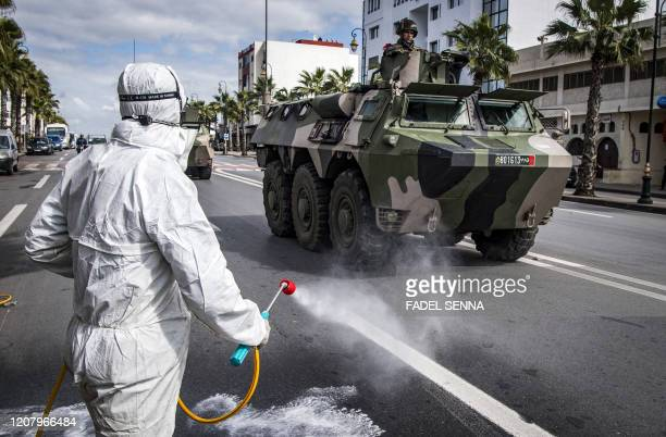 Health Ministry workers disinfect a street as a Moroccan military armoured personnel carrier patrols, instructing people to remain at home, in the...
