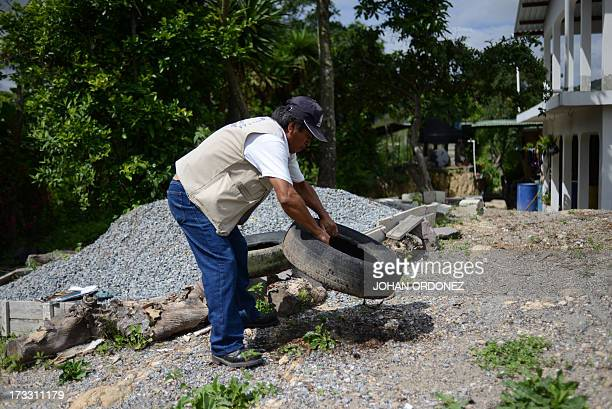 A Health Ministry's worker eliminates standing water where the Aedes aegypti mosquito vector of the dengue fever may breed around a house in the...