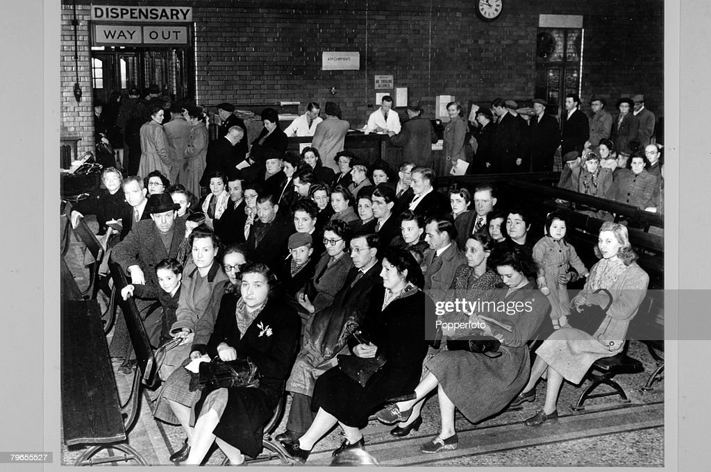 April 1949, Whitechapel, East London, Outpatients wait to see the doctors at the London Hospital, Other people in the background are fixing appointments and waiting for medicine