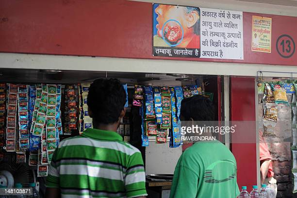 A health notice warning people against the dangers of tobacco is seen as people buy paan masala from a roadside vendor in New Delhi on July 10 2012...