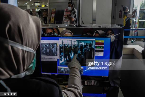 Health officer observes thermal scanner as the passengers from Singapore, China and Hong Kong arrived at Juanda International Airport in Surabaya,...