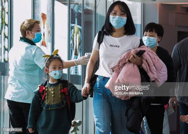 Health officer screens arriving passengers from China at Changi International airport in Singapore on January 22, 2020 as authorities increased...