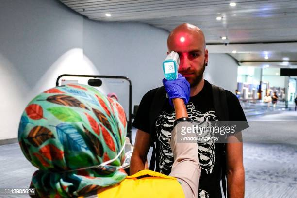 Health officer uses a thermal head to detect a monkeypox virus on arriving passengers at SoekarnoHatta International Airport in Tangerang near...
