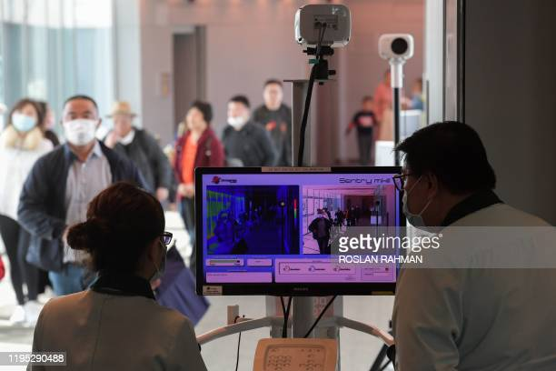 Health officers screen arriving passengers from China with thermal scanners at Changi International airport in Singapore on January 22 2020 as...