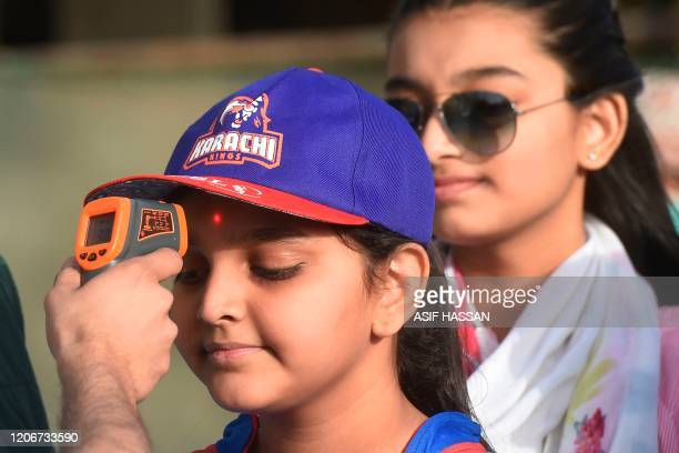 Health official checks the body temperature of a cricket fan amid concerns of the spread of the COVID-19 coronavirus at the entrance of the National...