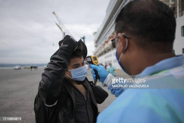 "Health official checks the body temperature of a passenger of the ""Caribbean Princess"" cruise at the port of Colon, in Panama, on May 28, 2020. -..."