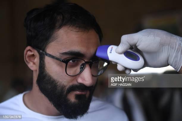 Health official checks the body temperature of a train passenger amid concerns over the spread of the COVID-19 novel coronavirus at Karachi...