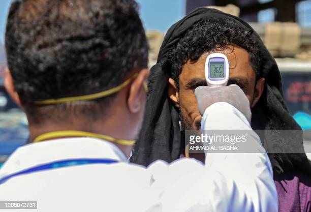 Health official checks the body temperature of man at the entrance of the city of Taez in southwestern Yemen on March 23, 2020 amid concerns over the...