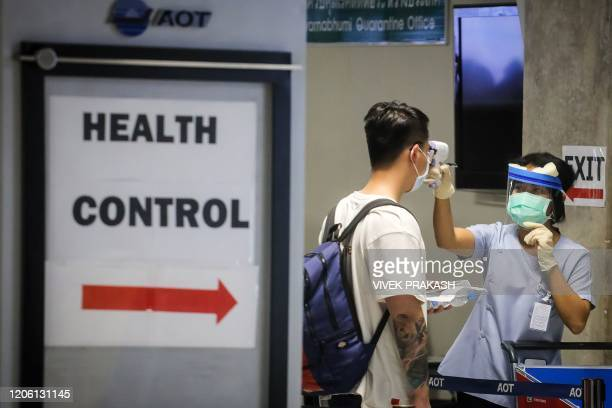 Health official checks the temperature of an incoming passenger during a health assessment at a checkpoint for people flying in from a list of...