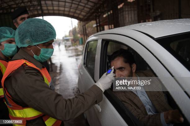 A health official of the Khyber Pakhtunkhwa emergency rescue service checks the body temperature of a government employee as a preventive measure...