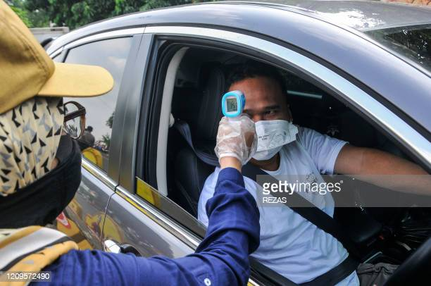 A health official scans a driver from Jakarta using a thermal gun following the implementation of large scale social restrictions at the border in...