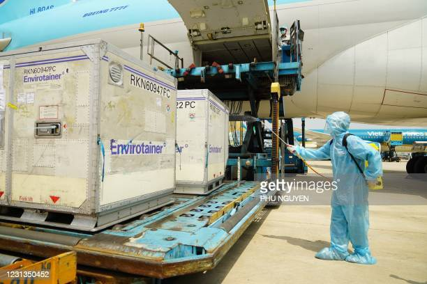 Health official sprays disinfectant on the first batch of AstraZeneca/Oxford Covid-19 coronavirus vaccine shipment after its arrival at the Tan Son...