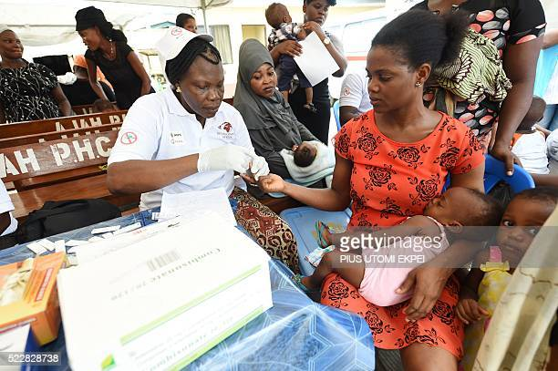 Health official takes blood sample of a mother for malaria testing at Ajah in Eti Osa East district of Lagos on April 21 2016 Dozens of patients and...