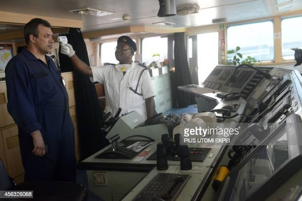 A Health official takes the body temperature of an Ukrainian sailor on the MV Pintail ship as they check for signs of the Ebola virus at the Apapa...