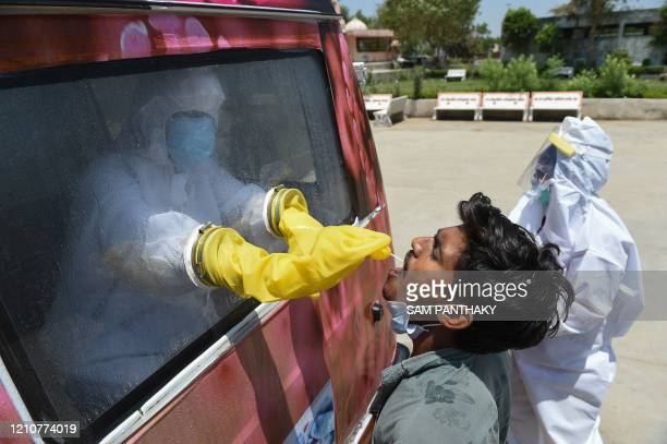 Health official uses a swab to collect a sample from a man for COVID-19 coronavirus testing from inside a mobile testing van during a...