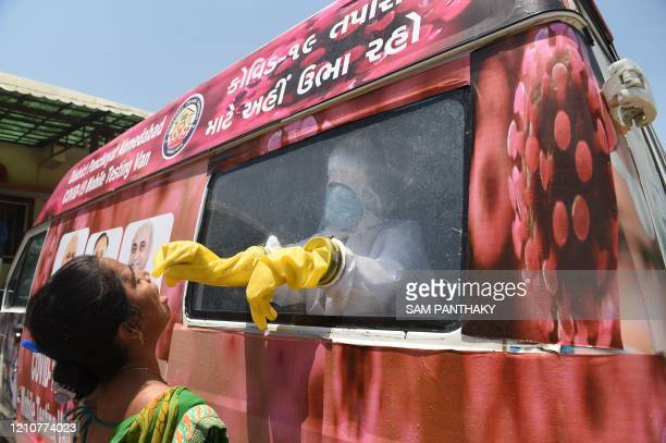 A health official uses a swab to collect a sample from a woman for COVID19 coronavirus testing from inside a mobile testing van during a...