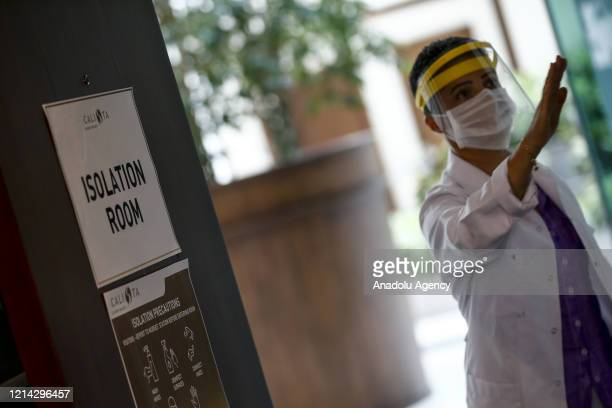 A health official wearing a mask is seen outside of an isolation room built for the patients in hotel during spring season amid coronavirus pandemic...
