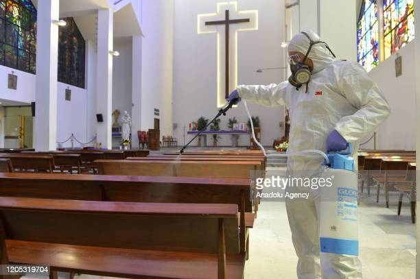 A health official wearing protective suit sprays disinfectant at a church as a precaution against the coronavirus in Beirut Lebanon on March 05 2020