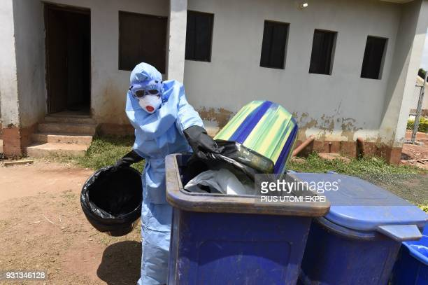 A health official wears protective gear to empty medical waste used for treating Lassa fever patients at the Institute of Lassa Fever Research and...