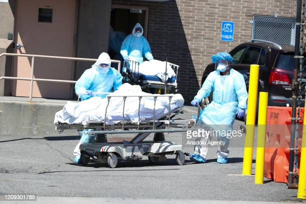 Health officials carry a dead body of coronavirus victim on a stretcher to container morgues by the Wyckoff Heights Medical Center in Brooklyn, New...