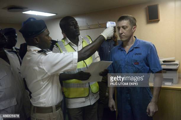 Health officials takes the body temperature of an Ukrainian sailor on the MV Pintail ship as they check for signs of the Ebola virus at the Apapa Sea...