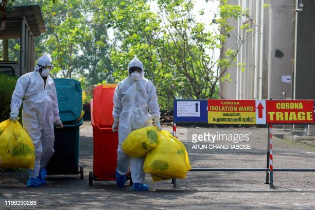 Health officials wearing protective clothing carry medical waste out of an isolation ward at the Ernakulam Medical College in Kochi on February 8,...