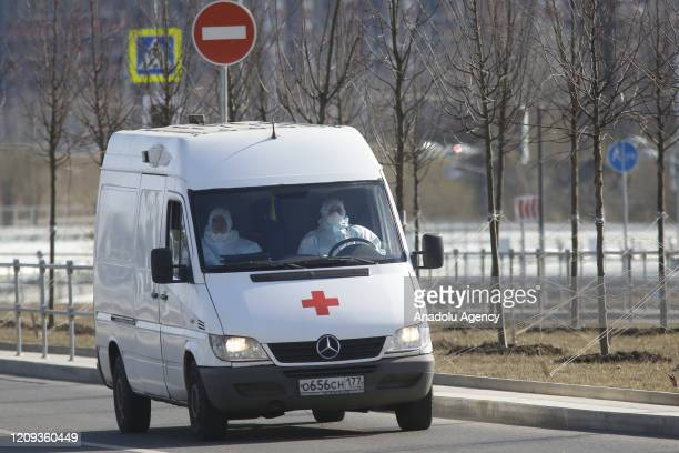 Health officials wearing protective suits transport a patient, who shows coronavirus symptoms, with an ambulance to Kommunarka Hospital, where...