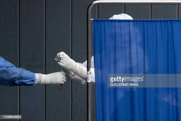 Health personal handle a sample as they run a test for COVID-19 behind a screen at the General Hospital in Tijuana, Baja California State, Mexico, on...