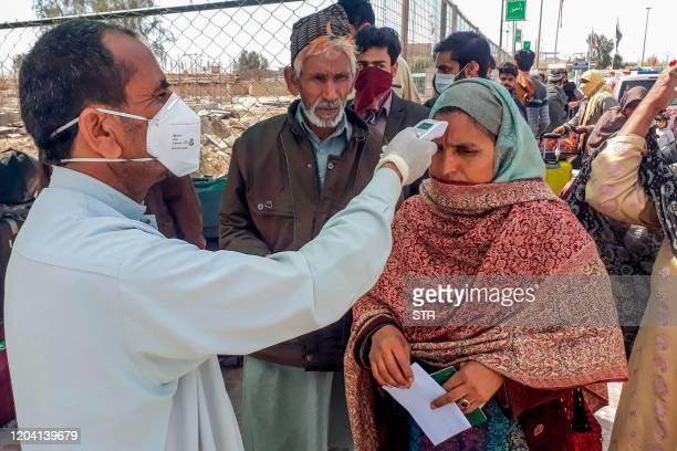 Health personnel checks the body temperature of a pilgrim returning from Iran via the Pakistan-Iran border town of Taftan on February 29, 2020. -...